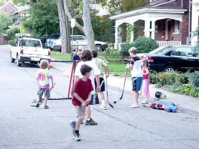 The children enjoy a good game of street hockey. (Photo Credit: Ryan McGreal)