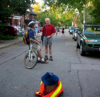 Back: Brian McHattie chats with a cyclist. Front: Officer Stumpy presides over the party. (Photo Credit: Jen Dawson)